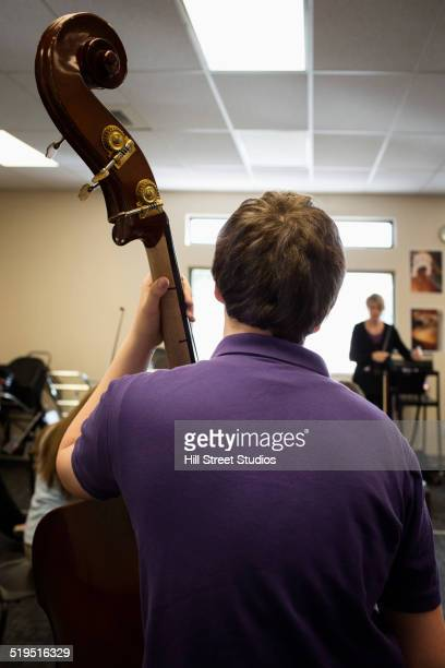 Caucasian boy playing upright bass