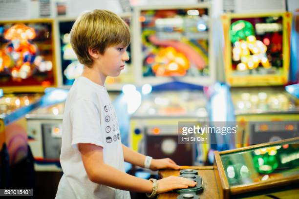 Caucasian boy playing video game in arcade