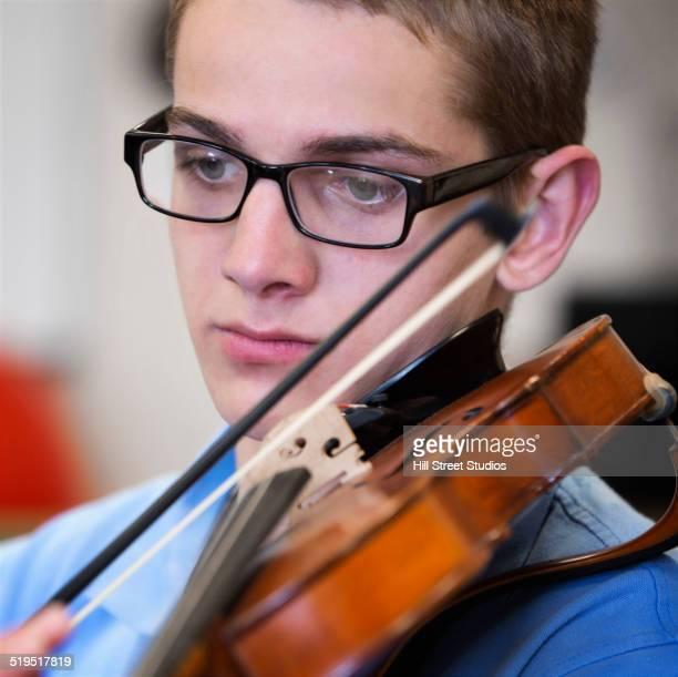 Caucasian boy playing violin
