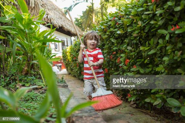 Caucasian boy playing with broom on path near house