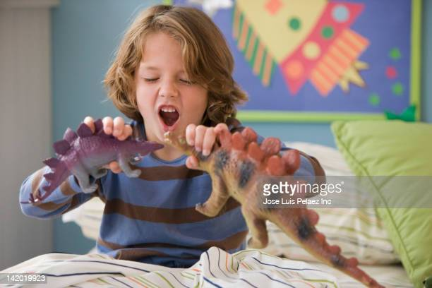 caucasian boy playing with dinosaurs on bed - dinosaur stock pictures, royalty-free photos & images