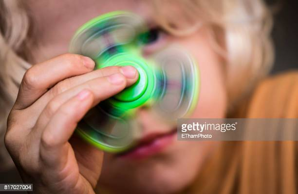 Caucasian boy playing with Fidget Spinner
