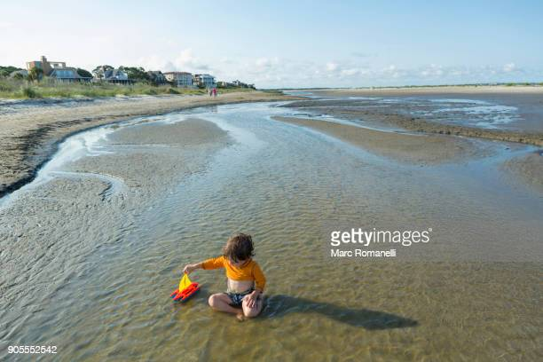 caucasian boy playing with sailboat in waves on beach - saint simon's island stock pictures, royalty-free photos & images