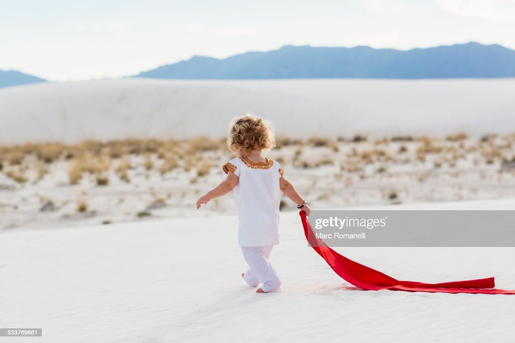 Caucasian boy playing with scarf on sand dune : Foto stock