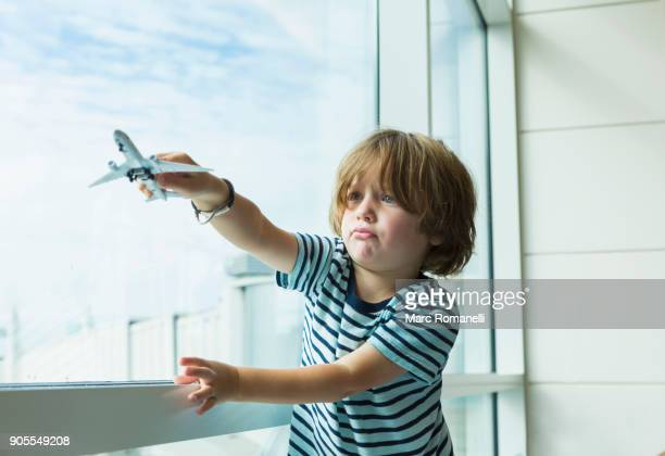 caucasian boy playing with toy airplane near window - kid in airport stock pictures, royalty-free photos & images