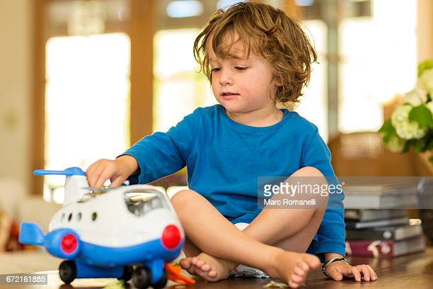 Caucasian boy playing with toy airplane on floor