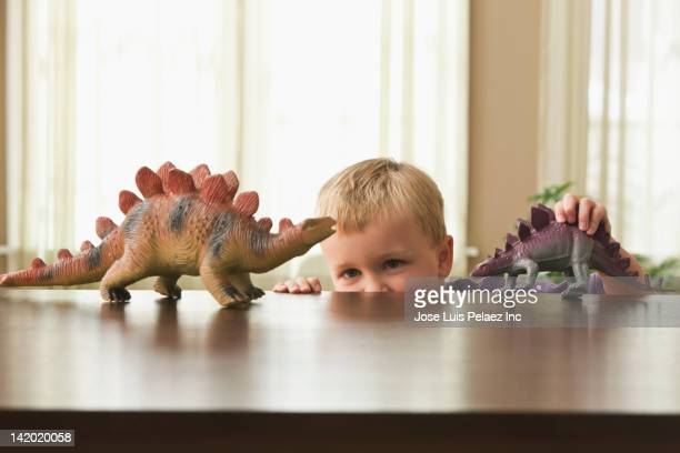 Caucasian boy playing with toy dinosaurs