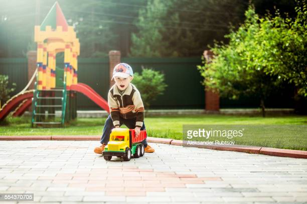 Caucasian boy playing with toy truck in playground