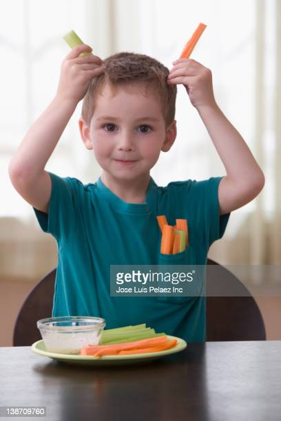 Caucasian boy playing with vegetables