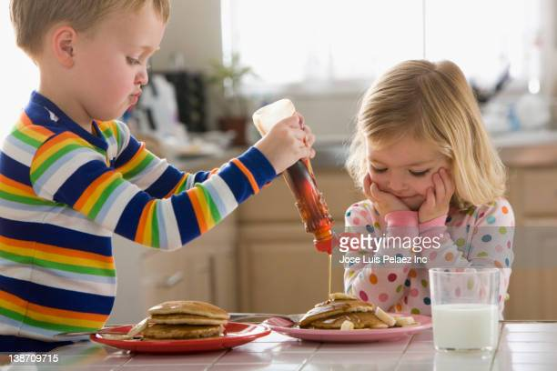 caucasian boy pouring syrup on sister's pancakes - groom human role stock pictures, royalty-free photos & images