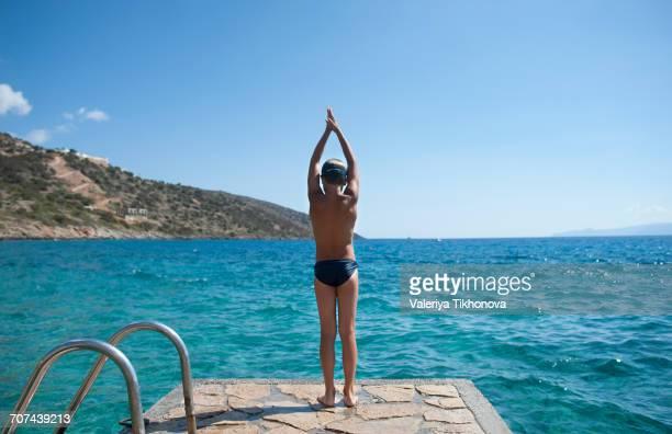 caucasian boy preparing to swim in lake - jungen in badehose 12 jahre stock-fotos und bilder