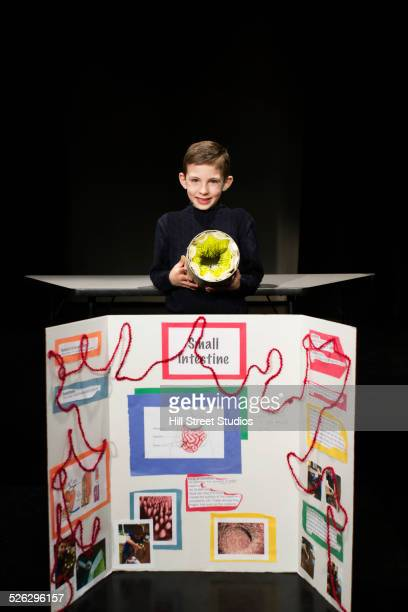 Caucasian boy presenting project at science fair