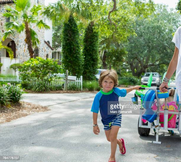 Caucasian boy pulling cart in street with mother