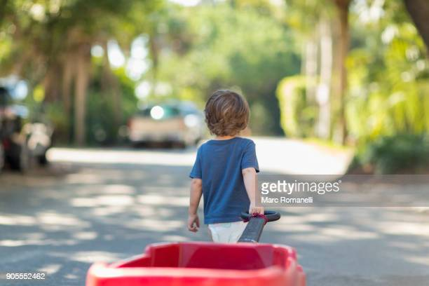 Caucasian boy pulling red wagon in street