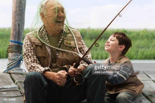caucasian boy putting fishing net over grandfather's head - naughty america stock pictures, royalty-free photos & images
