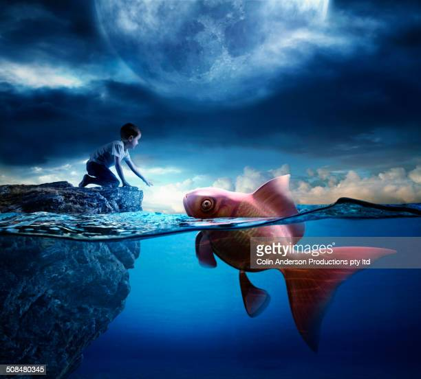 caucasian boy reaching for oversized goldfish in ocean - ethereal stock pictures, royalty-free photos & images
