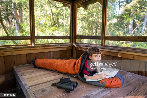 Caucasian boy reading in sleeping bag