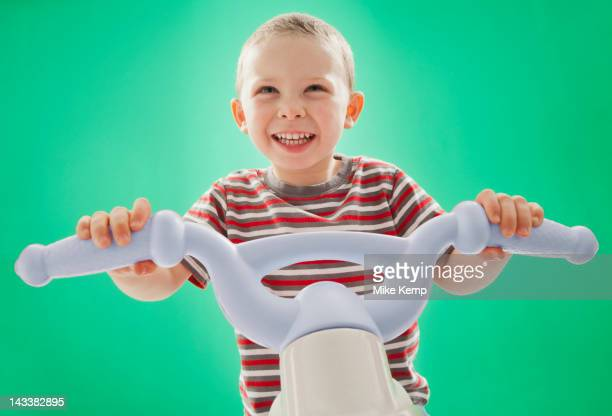 Caucasian boy riding plastic bicycle