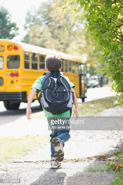 Caucasian boy running after school bus