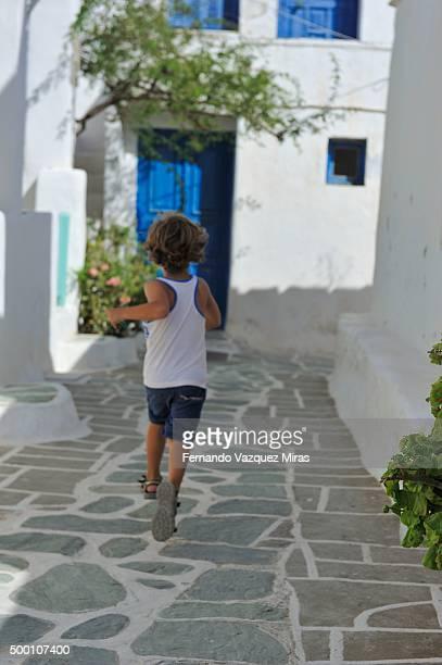 caucasian boy running at the kastro quarter. - lindos stockfoto's en -beelden