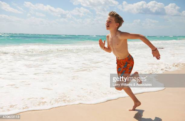 Caucasian boy running on beach