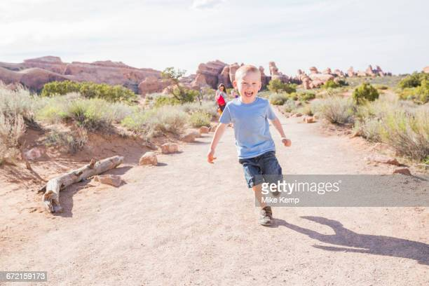 Caucasian boy running on dirt path