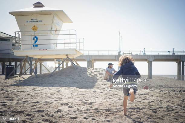 Caucasian boy running to father on beach
