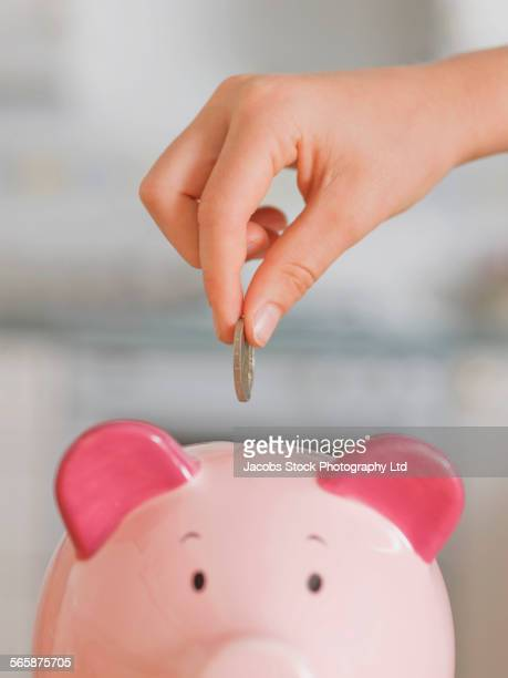 caucasian boy saving coin in piggy bank - piggy bank stock photos and pictures
