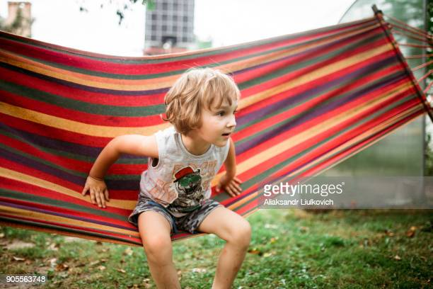Caucasian boy sitting in hammock