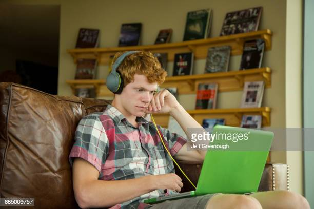 caucasian boy sitting on sofa listening to laptop with headphones - mood stream stock pictures, royalty-free photos & images