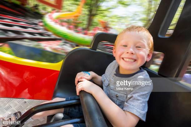Caucasian boy smiling on amusement park ride