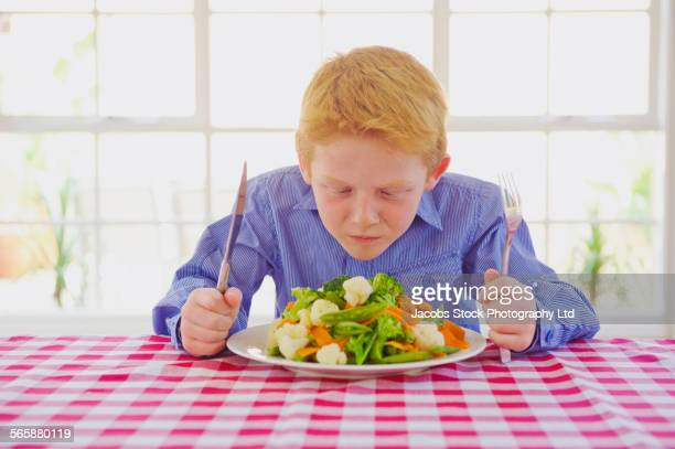 Caucasian boy sniffing vegetables at table
