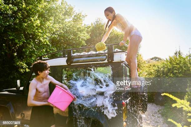 Caucasian boy splashing water from bucket on truck