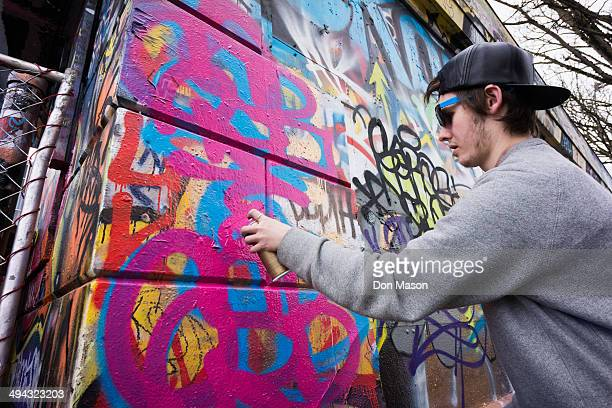 Caucasian boy spraying graffiti on urban wall