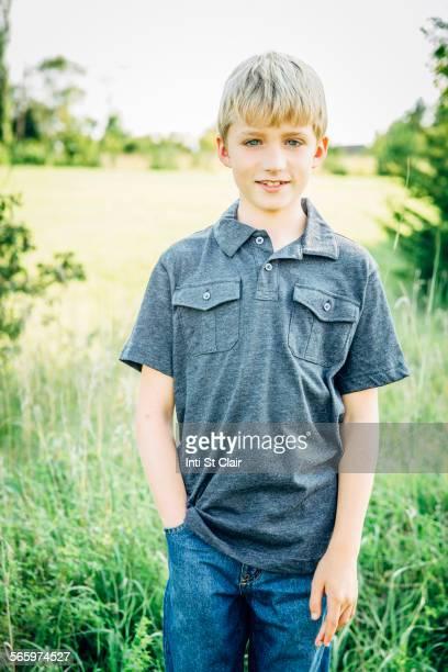 Caucasian boy standing in tall grass field