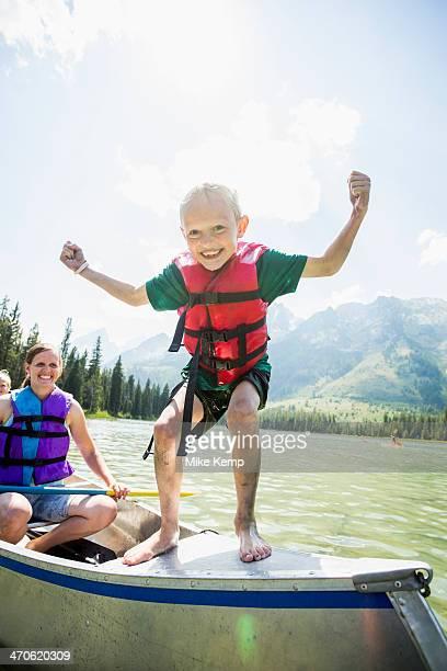 Caucasian boy standing on canoe on lake