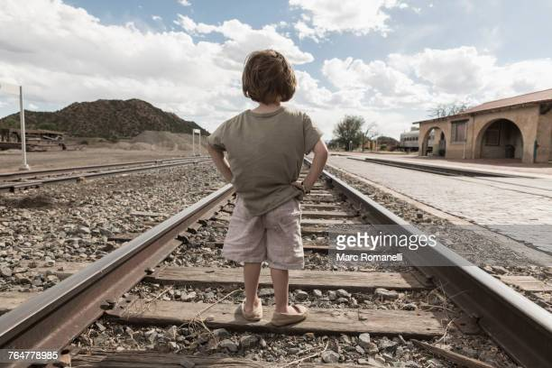 Caucasian boy standing with hands on hips on train track