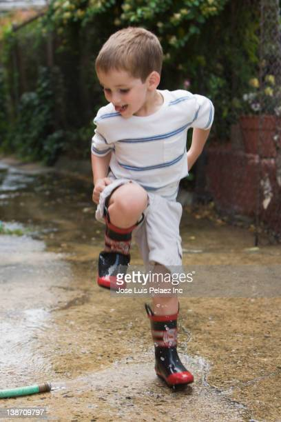Caucasian boy stomping in water puddle