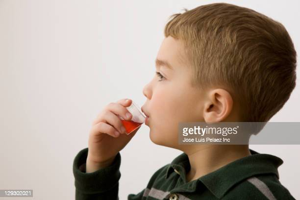 caucasian boy taking cough medicine - dose stock pictures, royalty-free photos & images