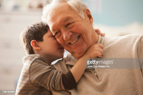 Caucasian boy telling grandfather a secret