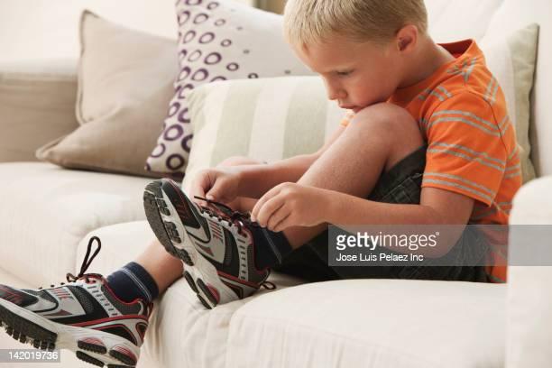 Caucasian boy tying shoes