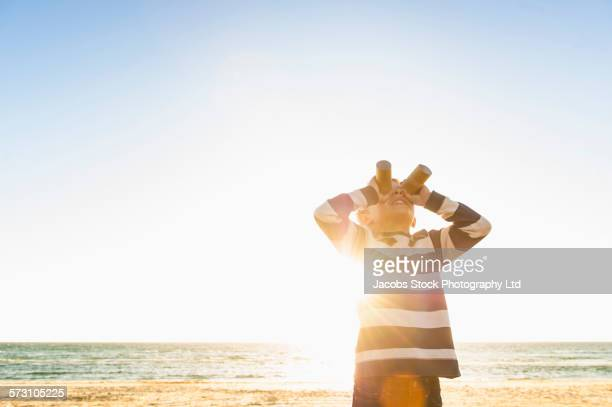 Caucasian boy using binoculars on beach