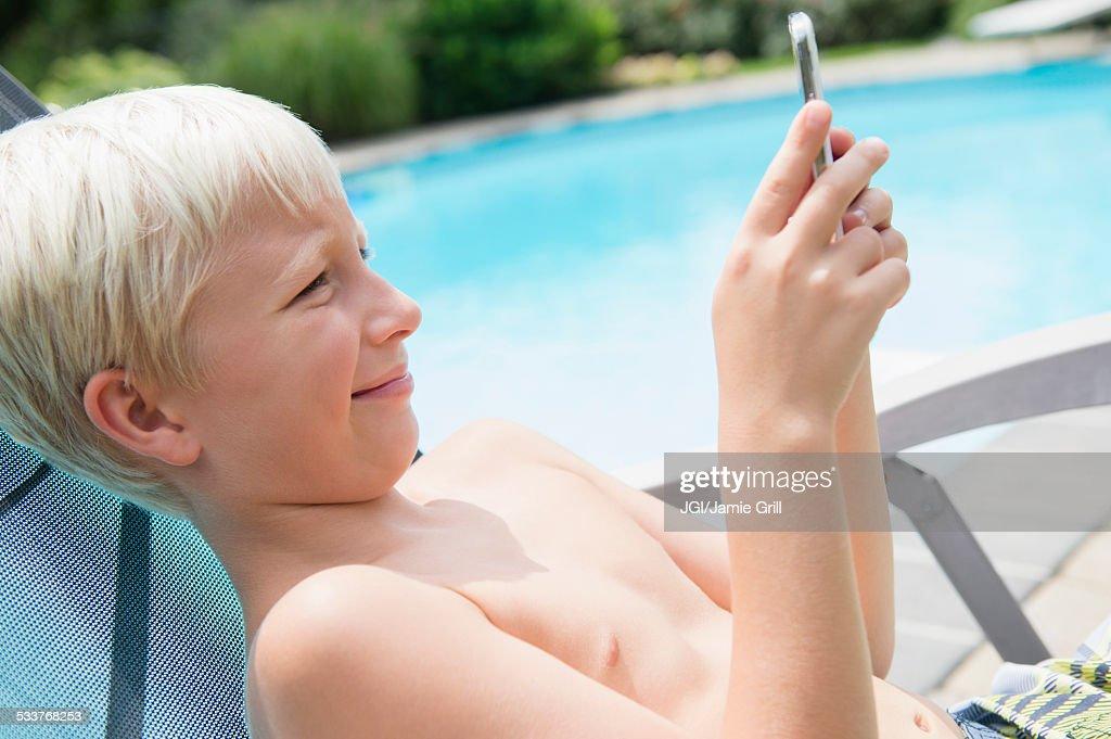 Caucasian boy using cell phone near swimming pool : Foto stock