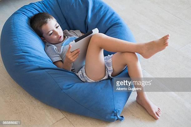 caucasian boy using digital tablet in beanbag chair - sacco photos et images de collection
