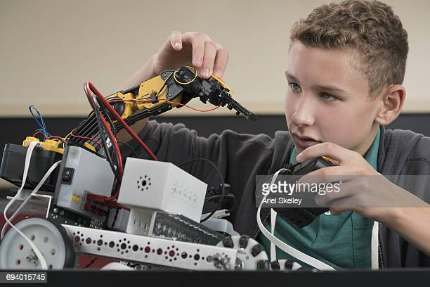 Caucasian boy using remote control with robot in robotics class
