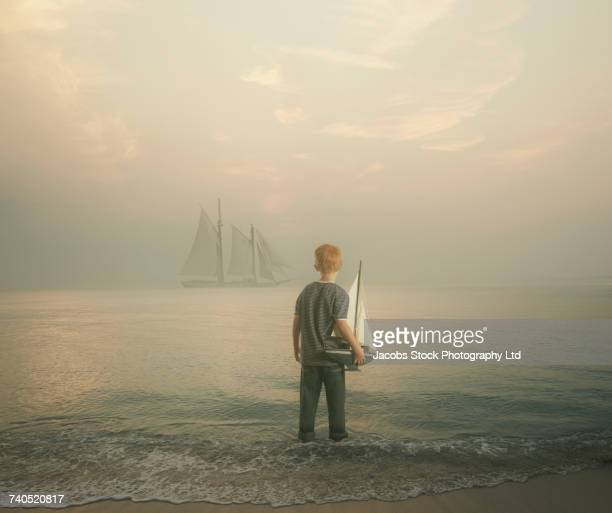 Caucasian boy wading in ocean holding toy boat admiring sailboat