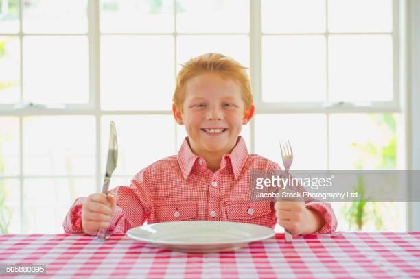 caucasian boy waiting to eat at table - faca faqueiro - fotografias e filmes do acervo