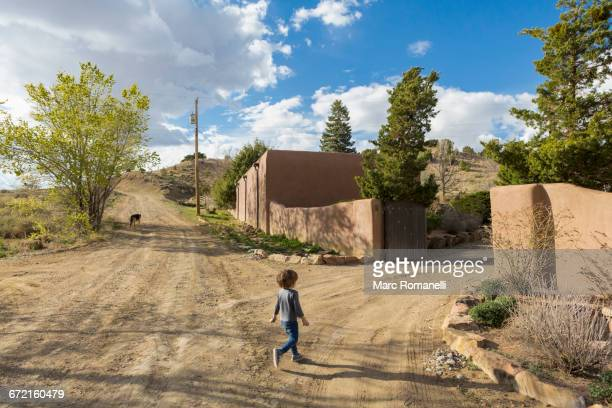 Caucasian boy walking on dirt road toward gate