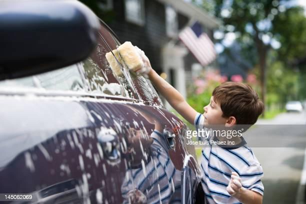 Caucasian boy washing car