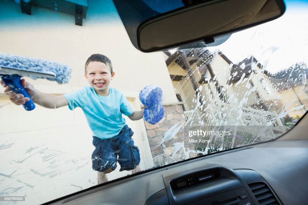 Caucasian boy washing car windshield : Foto stock